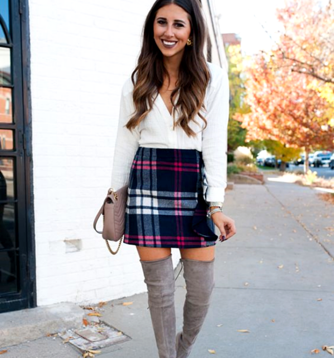 Brown-haired brunette girl wearing a white long-sleeved shirt, blue plaid Scottish-style mini skirt, long gray high-heeled boots, and beige handbag