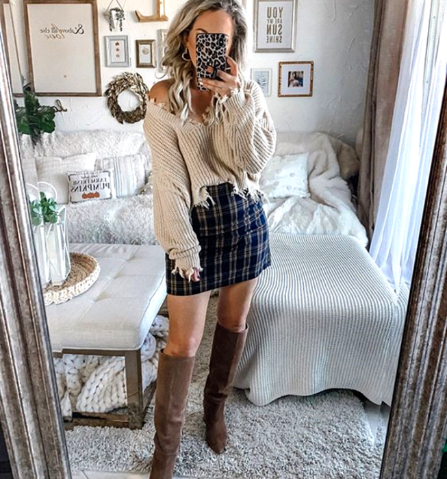 Platinum blonde girl wearing beige V-neck sweater, navy plaid Scottish mini skirt, brown long heeled boots