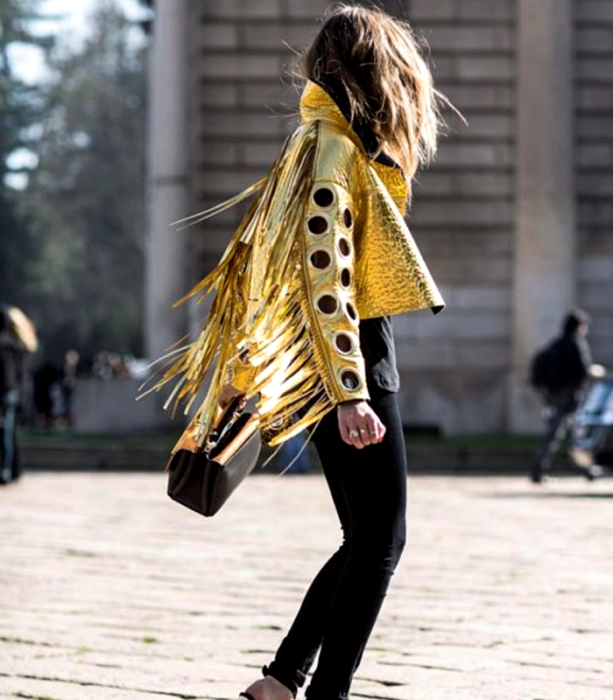 chica de cabello castaño usando una chamarra dorada metálica de manga larga con perforaciones en las mangas, skinny jeans negros, top negro y bolso de mano negro