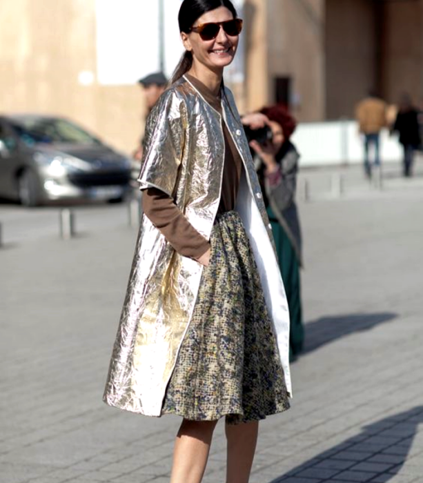brown haired girl wearing sunglasses, long sleeve brown top, light gold metallic long coat, beige patterned long skirt