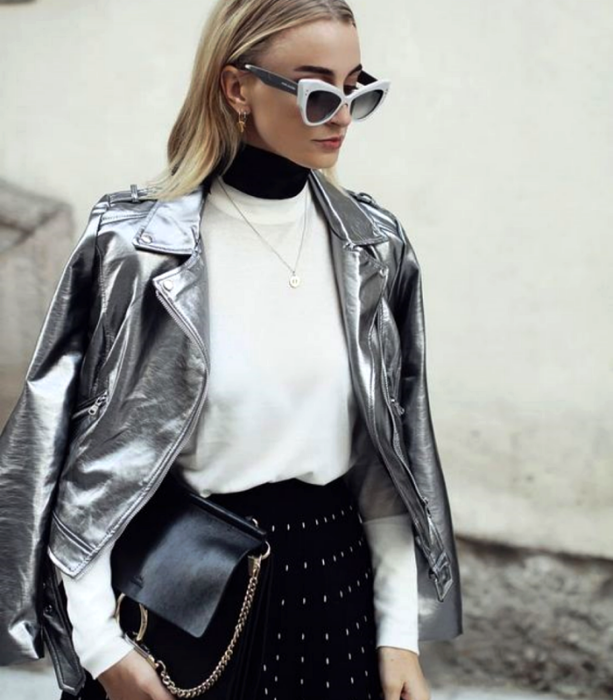 chica rubia usando lentes de sol blancos, suéter blanco, top negro de cuello alto, chamarra plateada metálica, minifalda negra con lunares blancos y bolso de mano negro