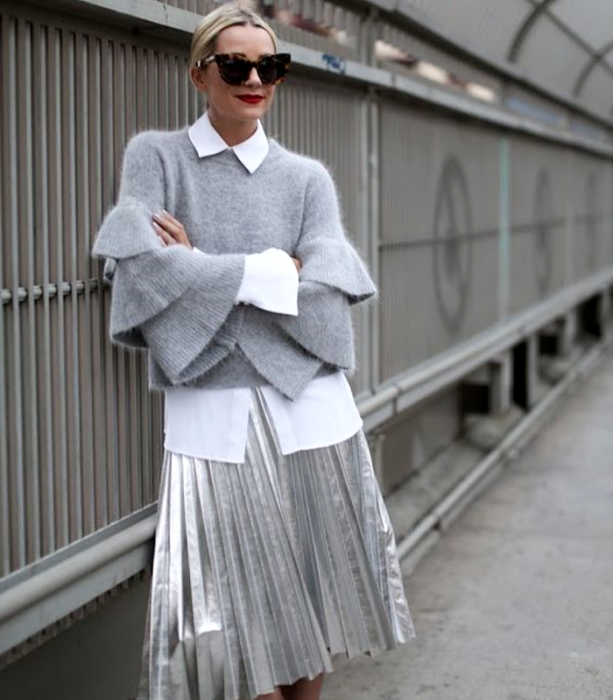 blonde girl wearing sunglasses, gray sweater with baggy sleeves, white dress shirt, long silver metallic plank skirt