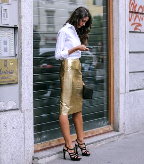 girl with long brown hair wearing a white dress shirt, gold metallic midi skirt, black heeled sandals and black clutch bag