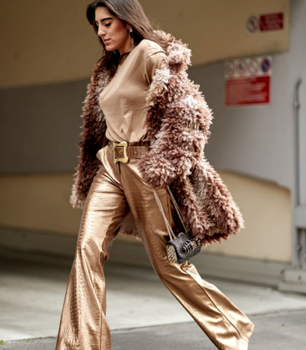 chica de cabello castaño usando un top café, abrigo teddy café afelpado, pantalones acampanados cafés metálicos y bolso de mano café con dorado