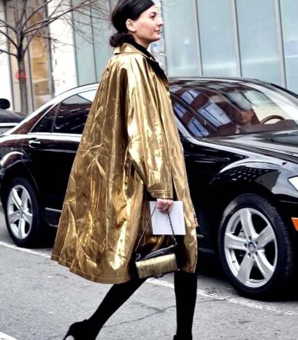 chica de cabello castaño usando un abrigo largo dorado metálico, bolso de mano negro con dorado metálico, medias negras gruesas y zapatos de tacón negros