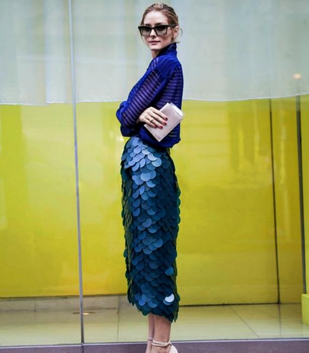 chica rubia usando lentes de sol, blusa de rayas azules semitransparentes, falda larga metálica color azul con escamas, bolso de mano beige y sandalias de tacón beige