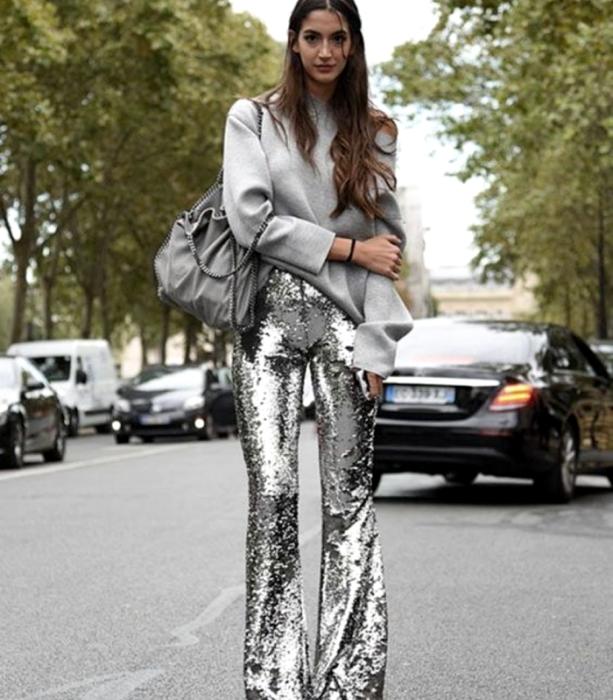 chica de cabello castaño usando un suéter gris oversized, bolso de mano gris, pantalones acampanados metálicos plateados