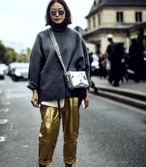 brown haired girl wearing sunglasses, gray turtleneck sweatshirt, silver metallic tote bag, metallic gold pants