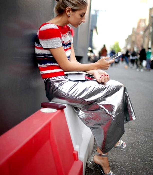 blonde girl wearing red, gray and blue striped knit top, silver metallic long skirt, silver metallic heeled sandals