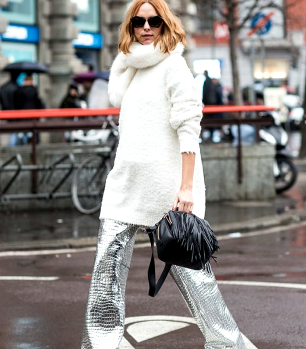 blonde girl wearing sunglasses, white high neck oversized sweater, silver metallic baggy pants and black tote bag