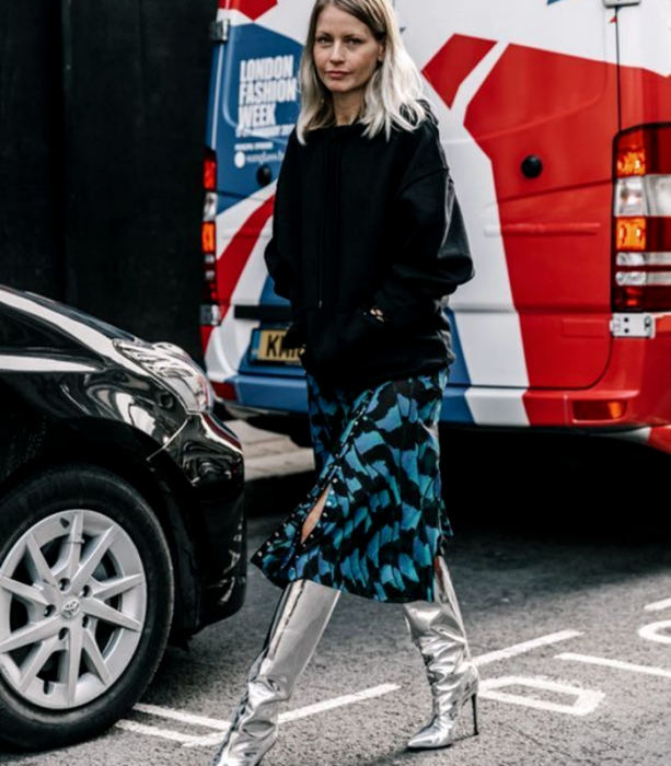 chica rubia usando un top negro de manga larga, falda midi azul con lineas negras, botas largas metálicas plateadas