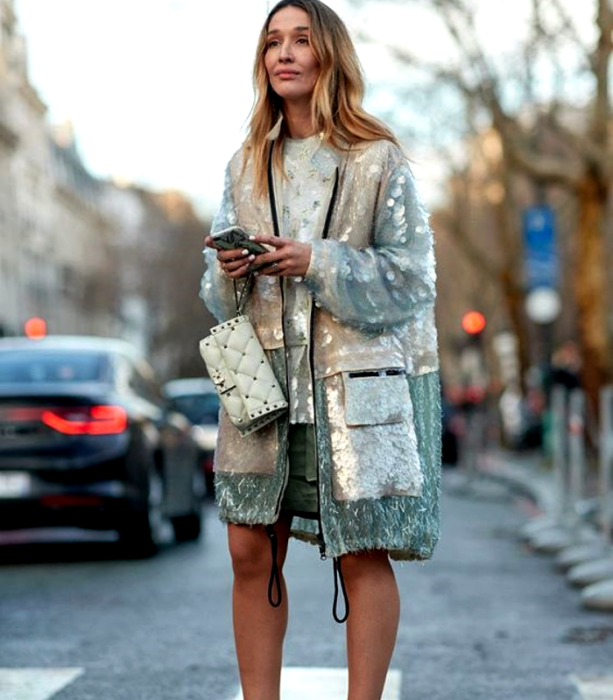 blonde girl wearing a metallic coat in beige, light blue and silver, white leather handbag