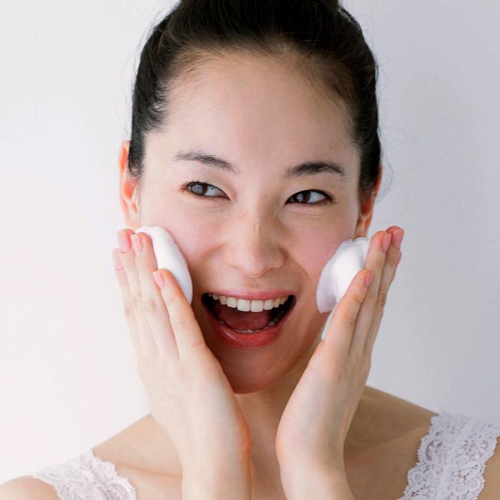 chica usando un limpiador facial