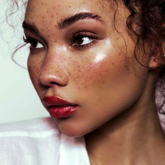 chica morena con cabello chino usando maquillaje sobre sus pecas naturales, lipstick rojo, blush rosa y sombras rosas