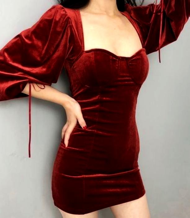 chica de cabello castaño usando un vestido de terciopelo rojo con mangas abombadas y escote de corazón