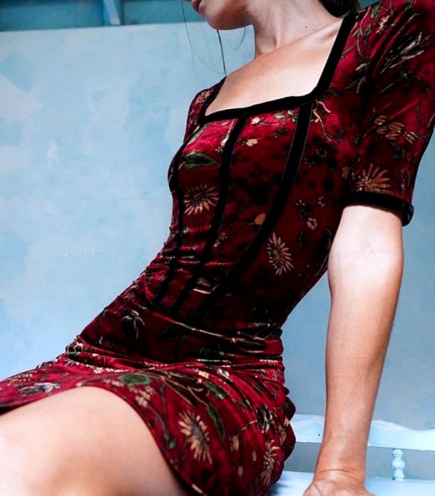 chica de cabello castaño usando un vestido de terciopelo rojo con mangas 3/4 y estampado de flores con lineas negras en el borde