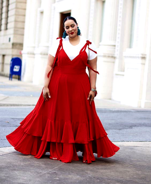 Curvy brunette girl in a red strap dress, V-neckline, white undershirt and skirt with ruffles
