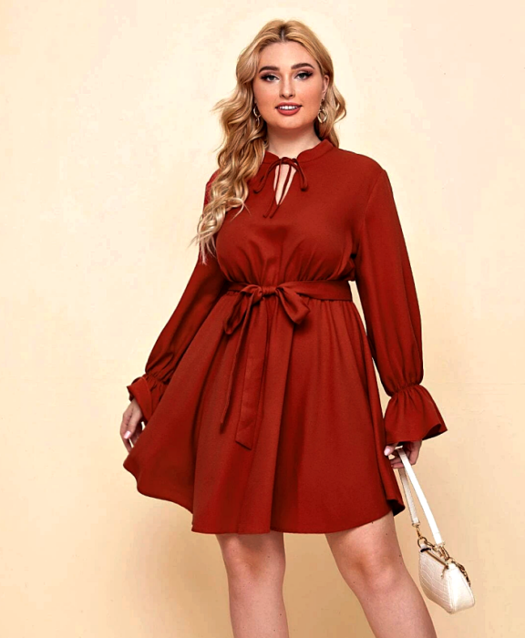 blonde girl wearing red dress with long sleeves, high neck, fit at the waist and white handbag