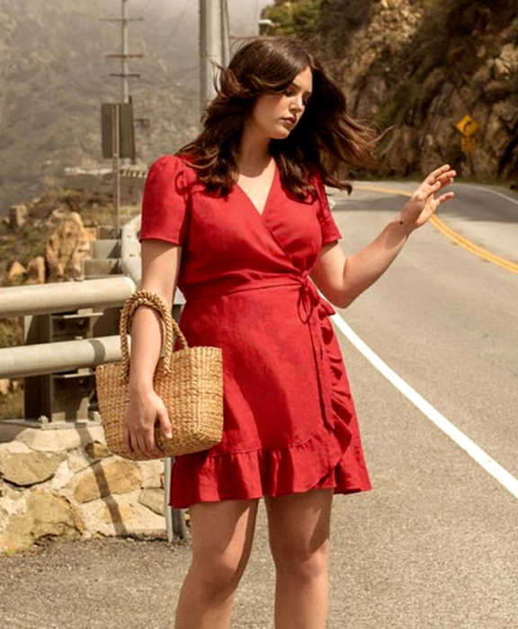 curvy girl with brown hair, wearing a red dress with short sleeves, V-neckline, fitted at the waist and raffia handbag