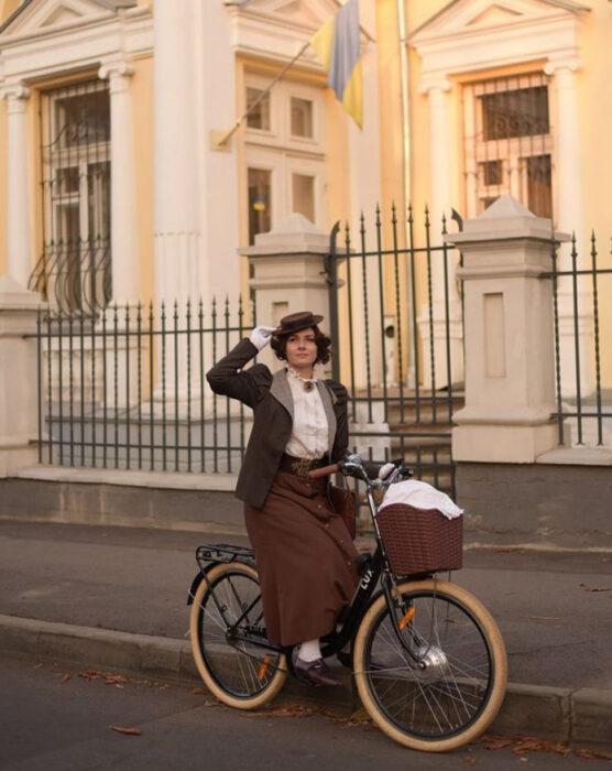 Mila Povoroznyuk usando atuendo de época, de falda larga color café, blusa blanca y saco gris, con cabello recogido y sombrero, montando una bicicleta