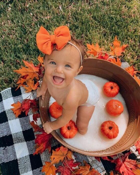 Bebé en una tina de madera con calabazas pequeñas, usando un moño naranja en la cabeza