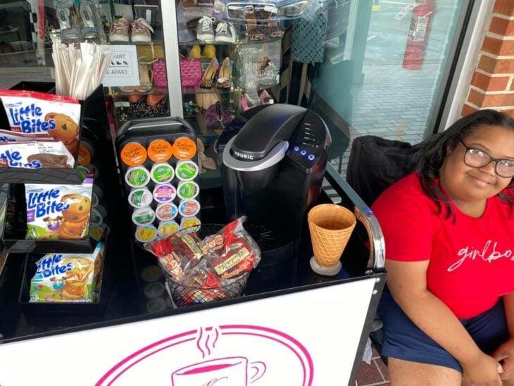 Kristina sentada en una silla al lado de su carrito de café