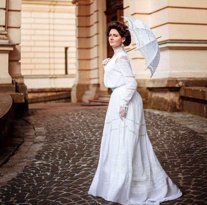 Mila Povoroznyuk usando un vestido de época de manga larga color blanco con una sombrilla del mismo color