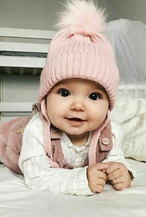 Bebé usando gorrito rosa, body blanco y jumper rosa palo