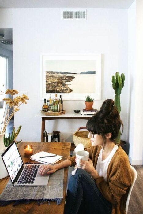 Chica trabajando en la computadora, su estudio tiene varias plantas en el lugar, como un cactus o una platita pequeña cerca de la computadora