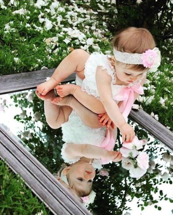 Bebé usando una diadema, con vestido blanco y sentada sobre un espejo viendo su reflejo