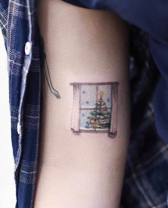 Girl with a window tattoo with a Christmas tree; Miniature tattoos for those who love Christmas
