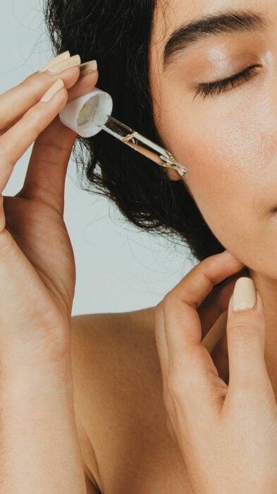 Chica aplicando algunas gotas de aceite de rosa mosqueta sobre su rostro