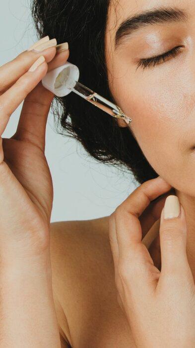 Girl applying some drops of rosehip oil on her face