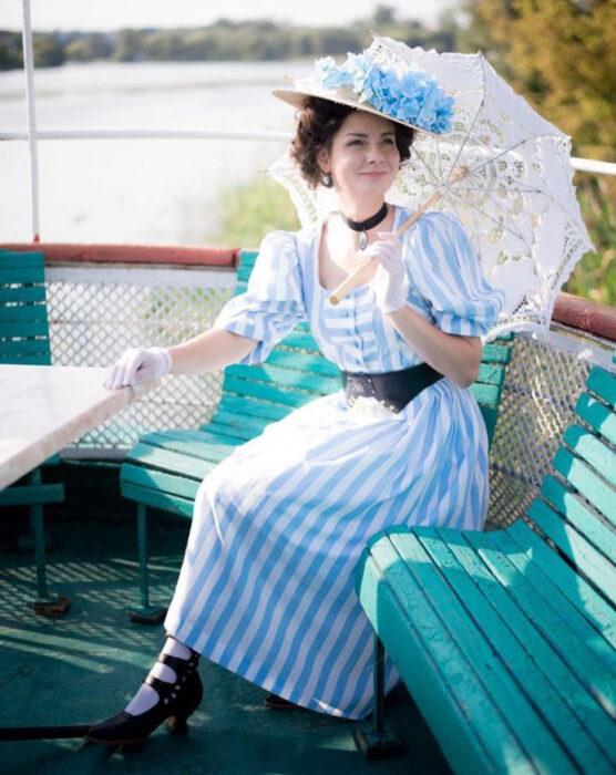 Mila Povoroznyuk usando atuendo de época, de vestido de rayas azul cielo con blanco, cinto negro, guantes blancos, sombrero y sombrilla
