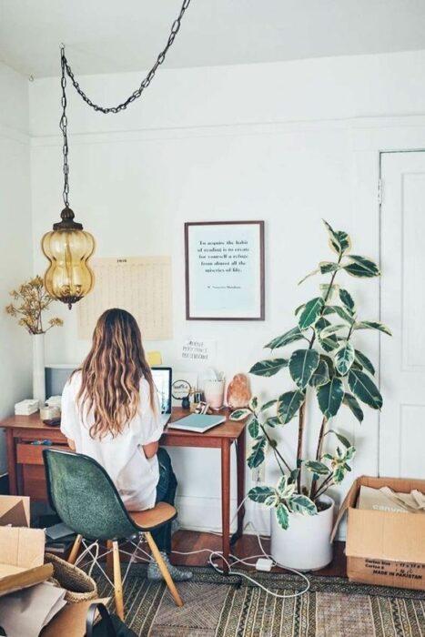 Chica trabajando en su espacio de trabajo en la que aparece una maceta con una planta alta