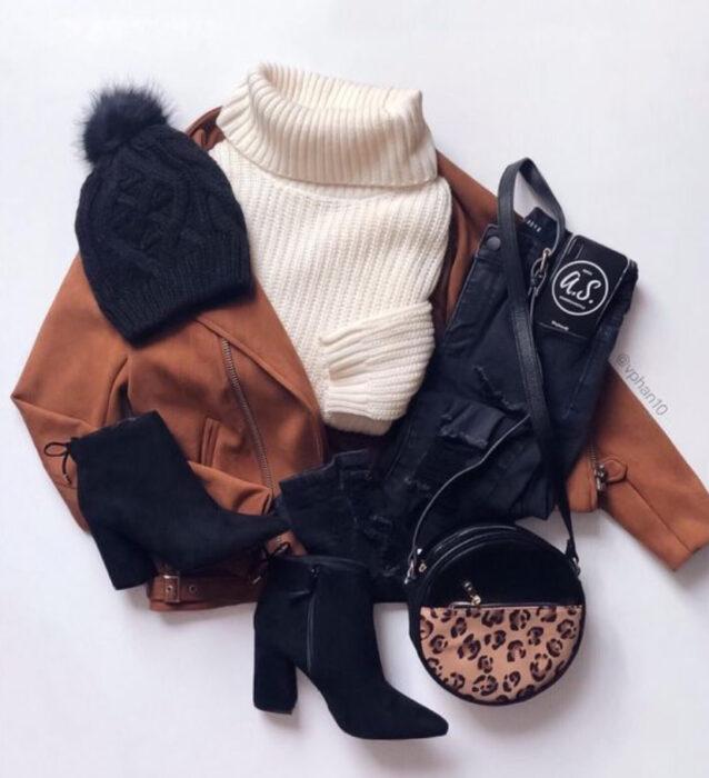 Chaqueta de cuero color camel, suéter color perla de cuello de tortuga, jeans negros, botas negras y bolso de mano