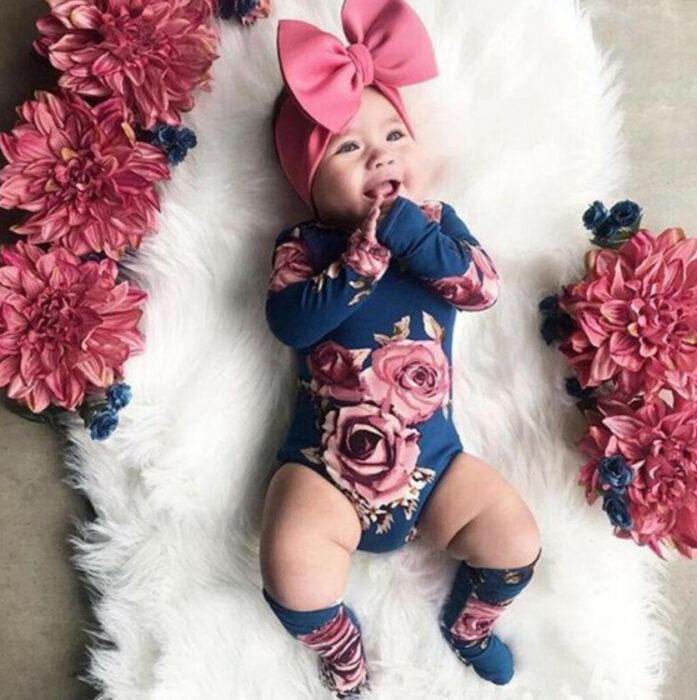 Bebé usando un moño rosa con un body de manga larga color azul marino y estampado de rosas