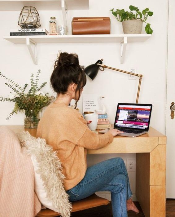Chica trabajando en la computadora, el lugar tiene una maceta con una planta