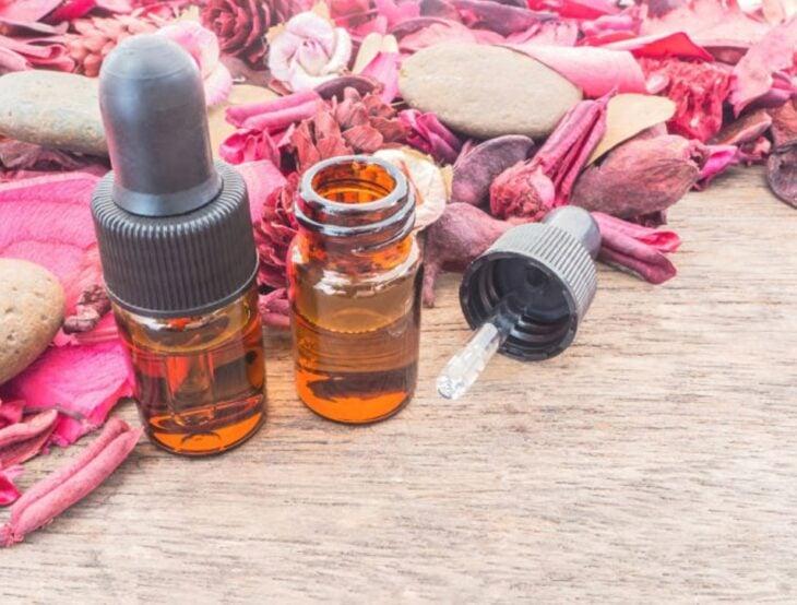 Frasquitos de aceite de rosa mosqueta con naturaleza muerta detrás de ellos