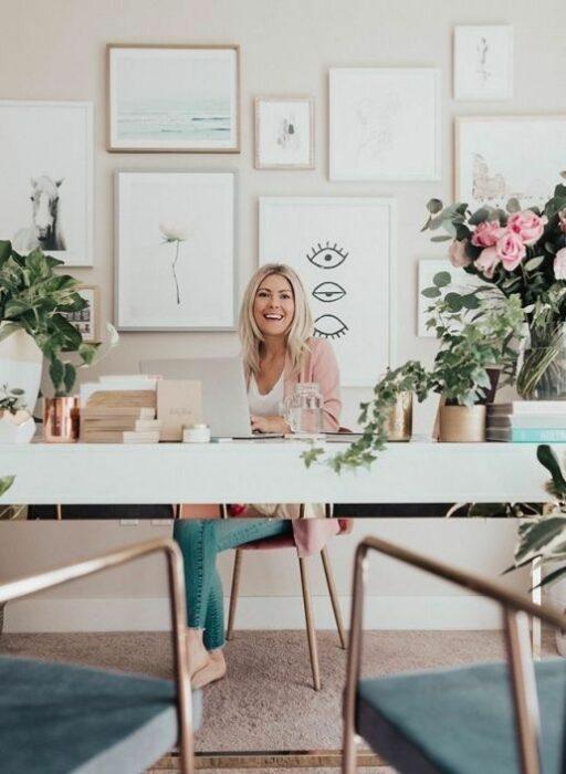 Chica trabajando en su escritorio que tiene varias macetas con plantas