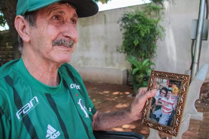 Altamir Soares de Oliveira mirando fotos de su hijo