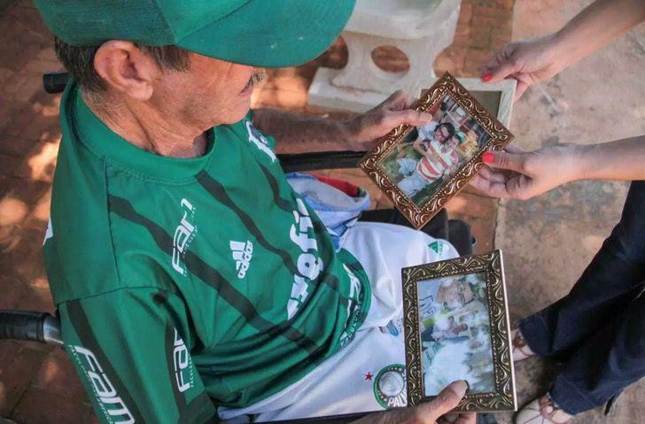 Altamir Soares de Oliveira mirando fotos de sus hijo