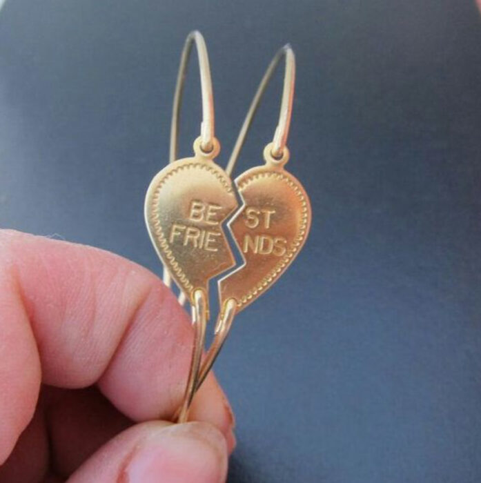 Friendship bracelets in gold color that have a heart-shaped charm that with the engraving of