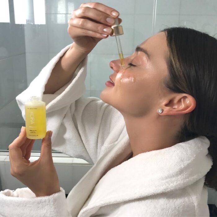 Miranda Kerr usando un aceite facial en su rostro con una bata de baño blanca