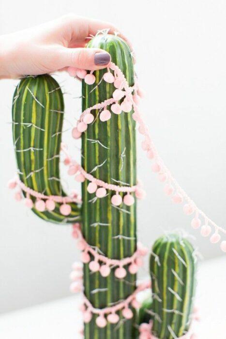 Cactus de adorno decorado con una guirnalda rosa pastel con bolitas
