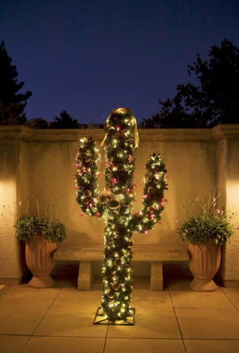 Árbol de navidad en forma de cactus colocado en el exterior de la casa decorado con luces amarillas y esferas rojas