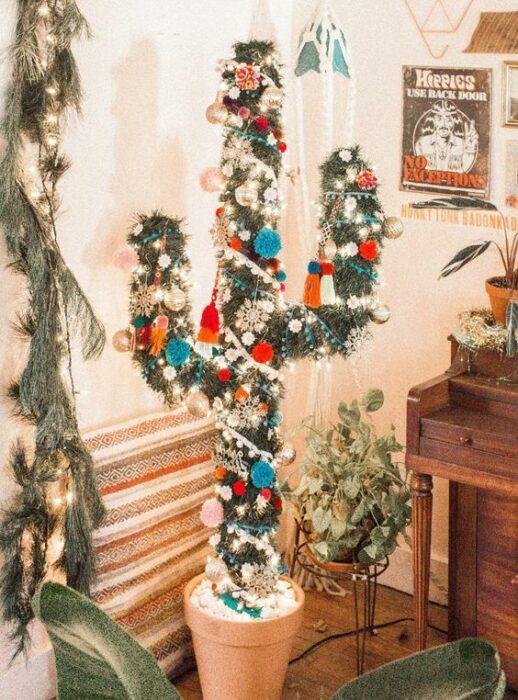 Árbol de navidad en forma de cactus  en una sala de paredes blancas con un mueble de madera en un costado