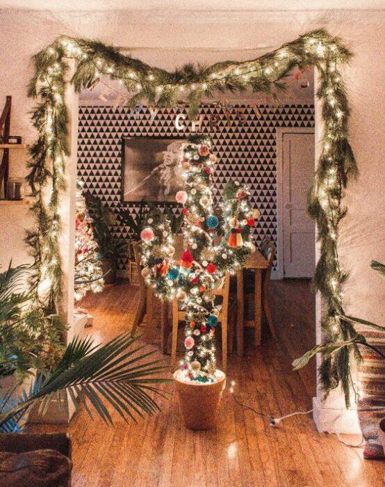 Árbol de navidad en forma de cactus en medio del comedor y la sala con ramas de pino y luces decorando la parte superior del techo