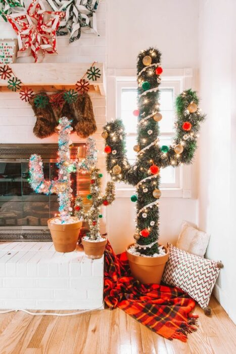 Árboles de navidad en forma de cactus de color verde y blanco en una sala con paredes blancas cerca de una chimenea