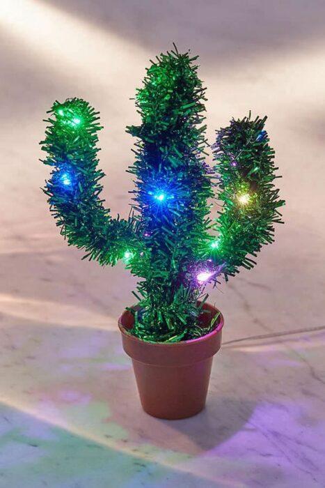 Árbol de navidad en forma de cactus pequeño en una maceta con luces azules y verdes